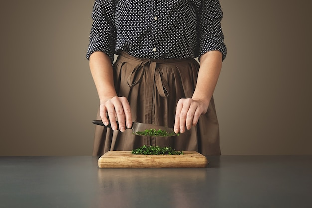 Kobieta trzyma nóż nad posiekaną zieloną pietruszką na desce na wieku niebieski stół. nie do poznania gospodyni domowa