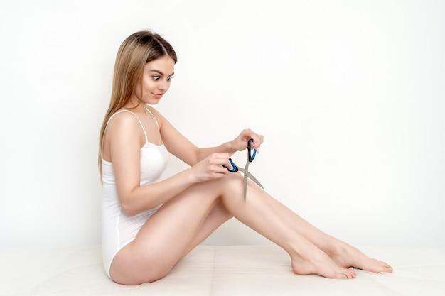 Kobieta trzyma nożyczki w pobliżu jej nóg.