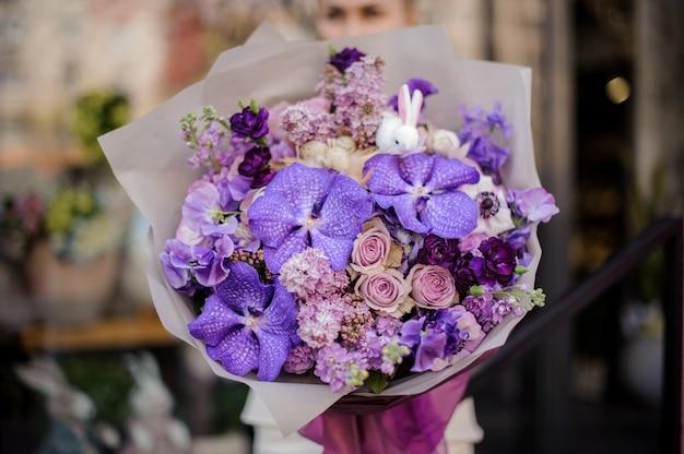 Kobieta trzyma ogromny bukiet delikatnych fioletowych kolorów kwiatów