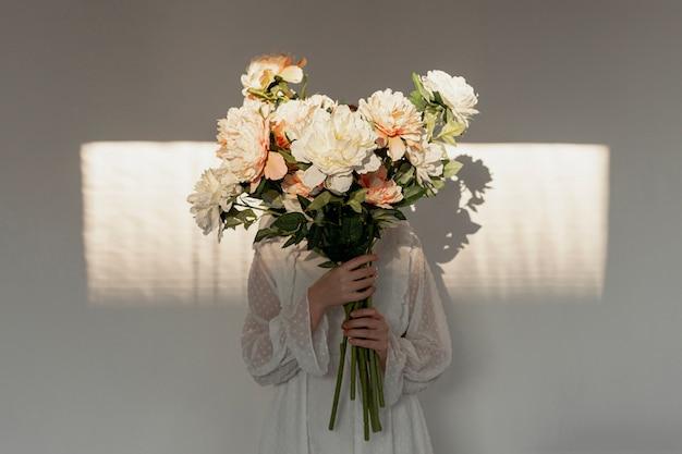 Kobieta trzyma ogromny bukiet kwiatów