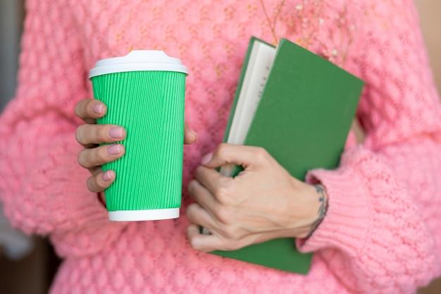 Kobieta trzyma otwartą książkę z bukietem suszonych kwiatów w środku i papierową filiżanką kawy