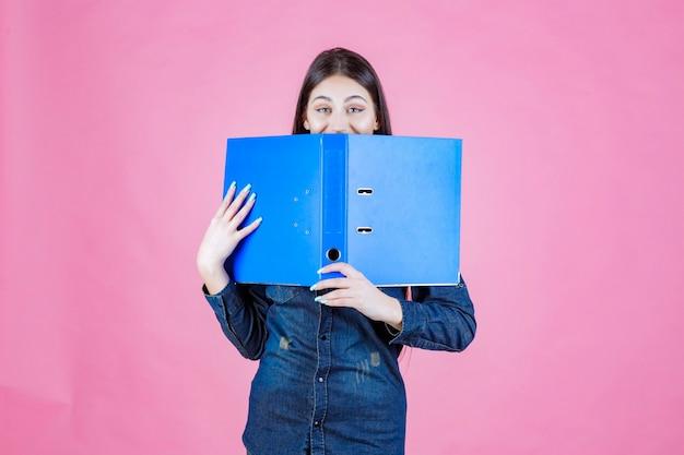 Kobieta trzyma otwarty folder projektu i ukrywa za nim twarz