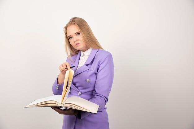 Kobieta trzyma otwarty tablet na biały.
