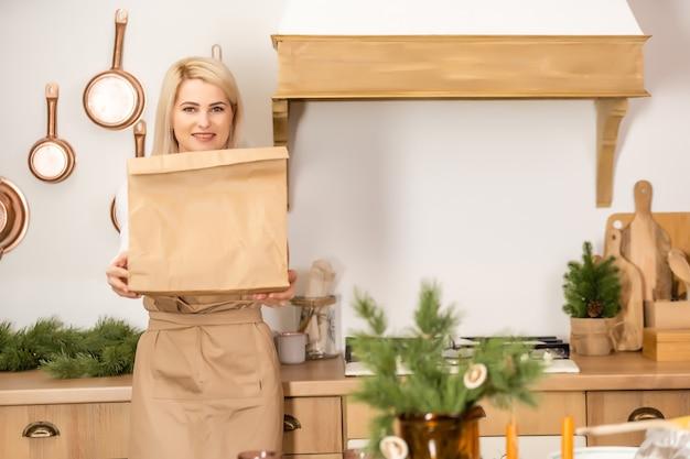 Kobieta trzyma pakiet dostawy żywności. pracownik przygotowujący jedzenie do dostawy w piekarni w okresie koronawirusa
