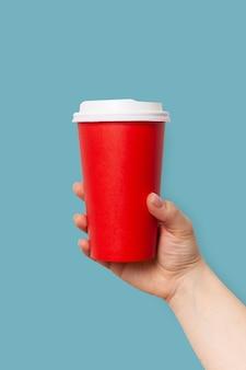 Kobieta trzyma papierową filiżankę kawy na wynos lub herbatę