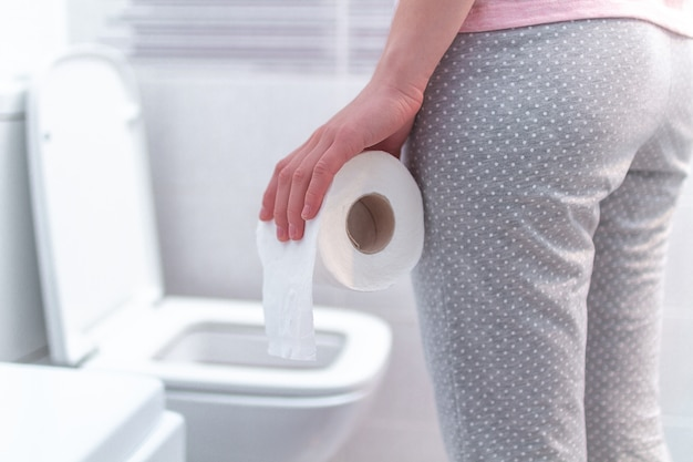 Kobieta trzyma papierową rolkę i cierpi na biegunkę, zaparcia i zapalenie pęcherza moczowego w toalecie. ból brzucha podczas pms. opieka zdrowotna