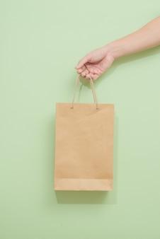 Kobieta trzyma papierową torbę na zakupy na zielonym tle