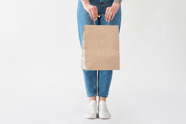 Kobieta trzyma papierową torbę z sklepami spożywczymi w cajgach