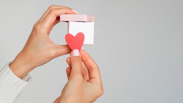 Kobieta trzyma papierowe serce i pudełko