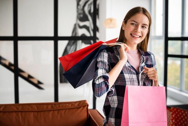 Kobieta trzyma papierowe torby i patrzeje daleko od