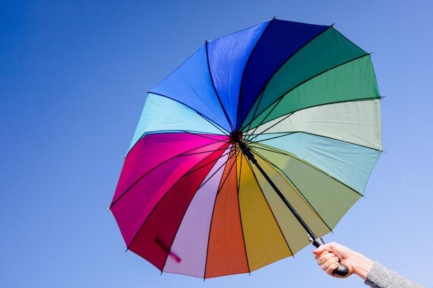 Kobieta trzyma parasol o żywych kolorach na tle jasnego nieba.
