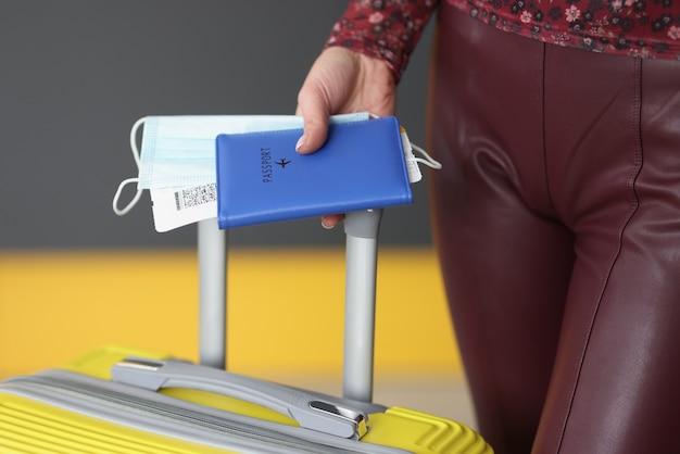 Kobieta trzyma paszport, bilet lotniczy, maskę medyczną i walizkę, bezpieczne loty i koncepcję odprawy