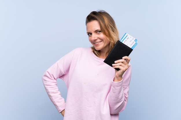Kobieta trzyma paszport nad błękit ścianą