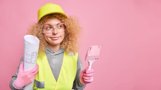 Kobieta trzyma pędzel, a plan odwraca wzrok, żeby zrobić remont domu house