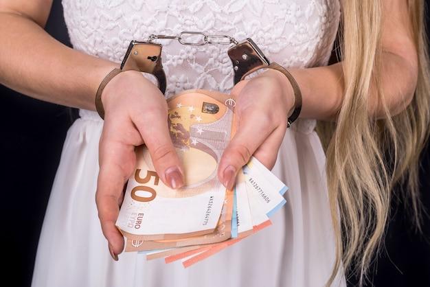 Kobieta trzyma pieniądze euro w kajdankach