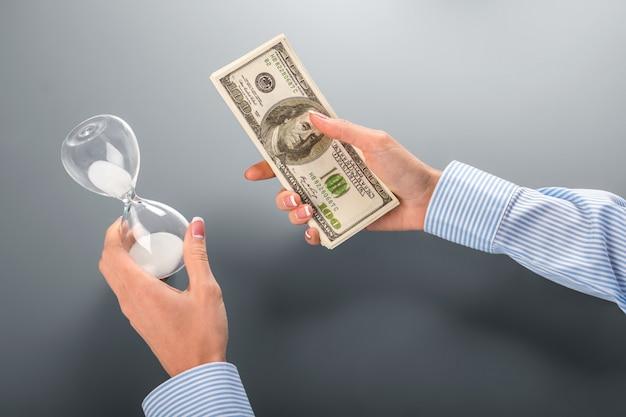 Kobieta trzyma pieniądze i klepsydrę. kobieta trzyma gotówkę i klepsydrę. doceń to, co masz. weź jedną lub obie.