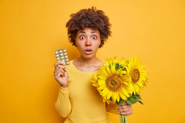 Kobieta trzyma pigułki i bukiet słoneczników uczulenie na pyłki ma czerwone opuchnięte łzawiące oczy katar pozy na jaskrawożółte