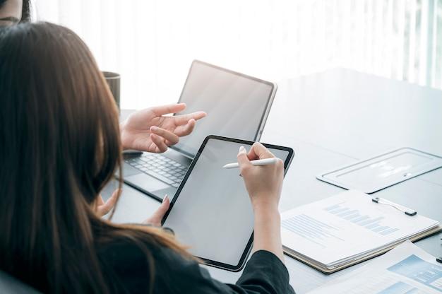 Kobieta trzyma pióro cyfrowe, wskazując na ekranie tabletu podczas pracy z zespołem w nowoczesnym biurze.