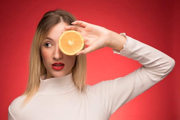 Kobieta trzyma plasterek pomarańczy nad jej okiem