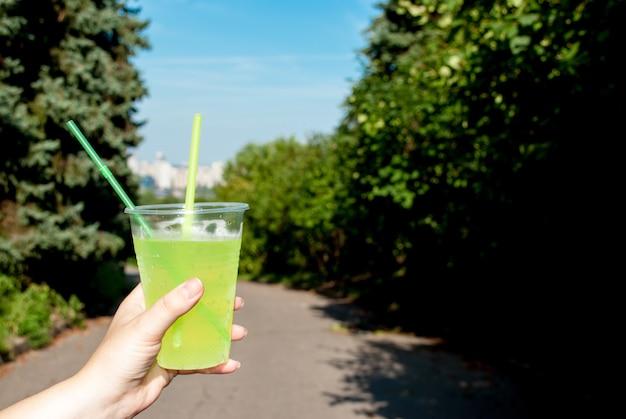 Kobieta trzyma plastikowy zielony koktajl kubek zbliżenie, na zewnątrz latem w parku.