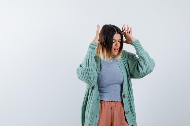 Kobieta trzyma podniesione ręce blisko głowy w zwykłych ubraniach i wygląda na zirytowaną, widok z przodu.
