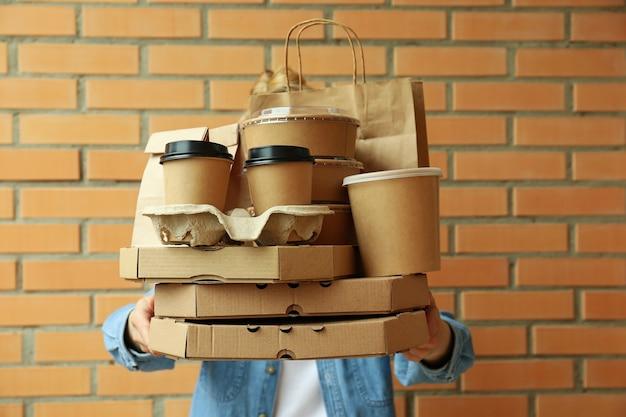 Kobieta trzyma pojemniki dostawcze na jedzenie na wynos na powierzchni ściany z cegły