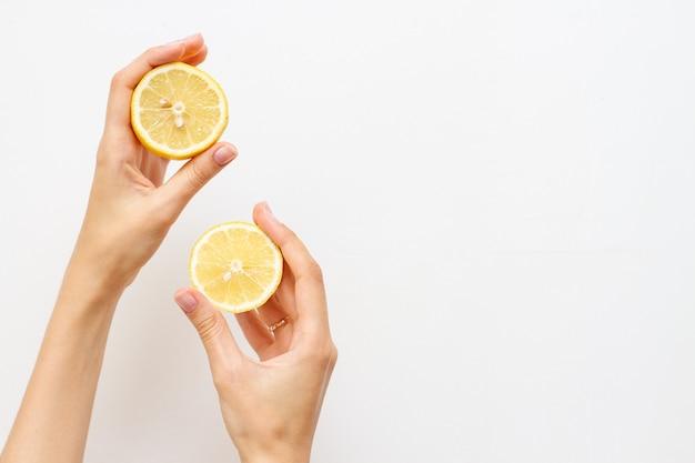 Kobieta trzyma połowę świeżej cytryny, wolne miejsce na tekst.