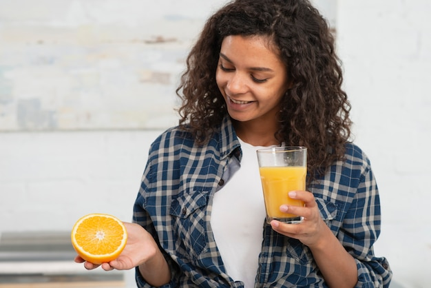 Kobieta trzyma pomarańczę i szklankę soku