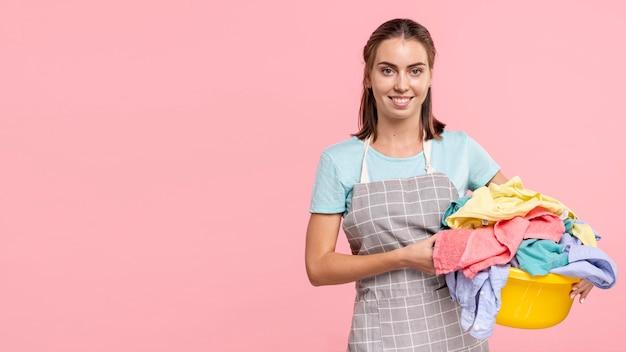 Kobieta trzyma pralnianego kosz z fartuchem