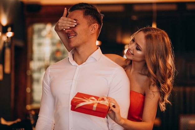 Kobieta trzyma prezent dla swojego chłopaka na walentynki