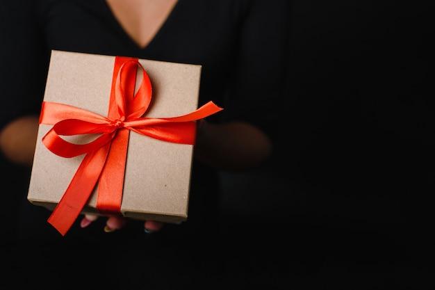 Kobieta trzyma prezent gwiazdkowy z czerwoną wstążką