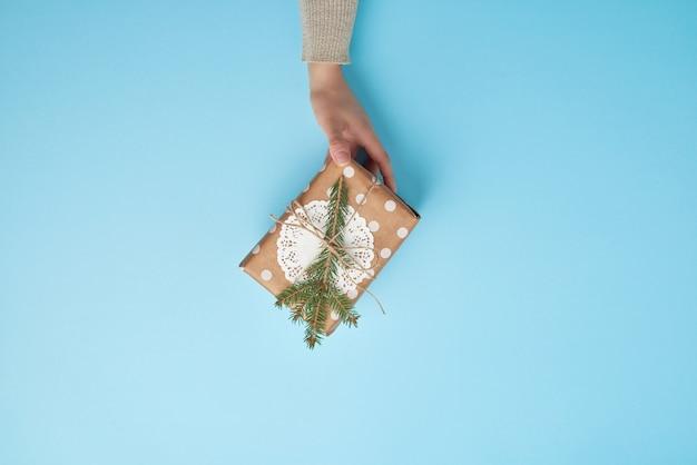 Kobieta trzyma prezent owinięty w brązowy papier i ozdobiony liną