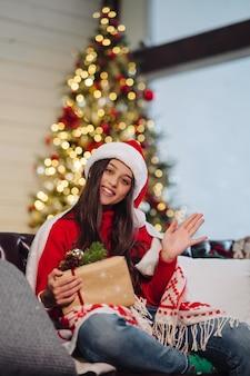 Kobieta trzyma prezent pod choinkę w boże narodzenie.