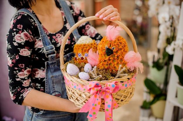 Kobieta trzyma prezent wielkanocny składający się z wiklinowego kosza z kurczakiem i jajkiem w kształcie kwiatów