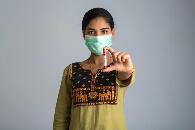 Kobieta trzyma probówkę z próbką krwi do koronawirusa lub analizy 2019-ncov.