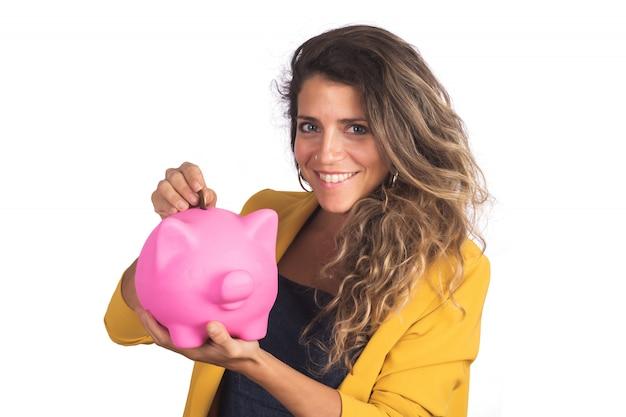 Kobieta trzyma prosiątko banka na studiu.