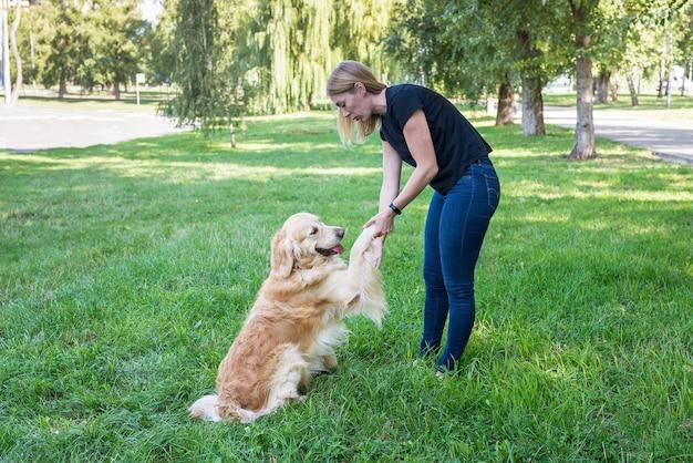 Kobieta trzyma psa retrievera za przednie łapy w parku