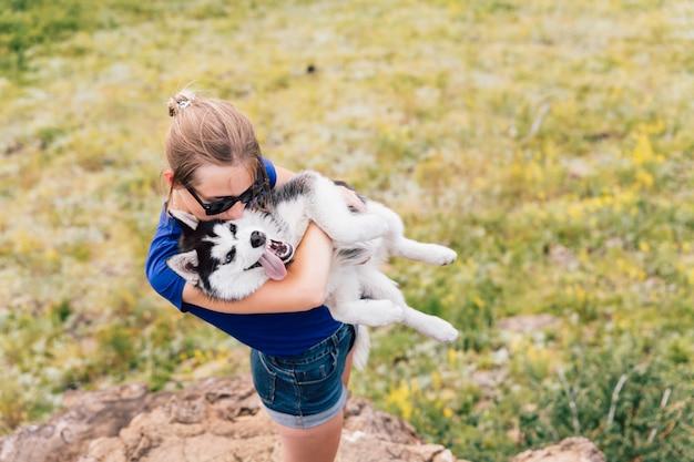 Kobieta trzyma psa w ramionach. husky w naturze.