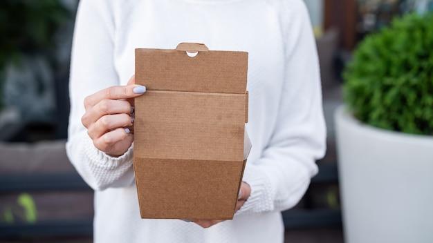 Kobieta trzyma pudełko na żywność z papieru nadającego się do recyklingu. pomysł na recykling