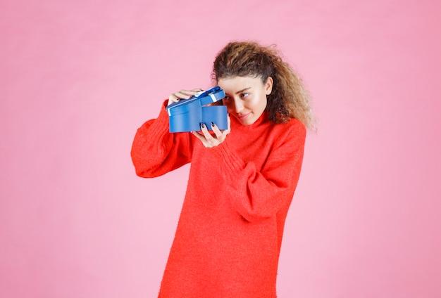 Kobieta trzyma pudełko upominkowe w kształcie niebieskiego serca i otwierając je.