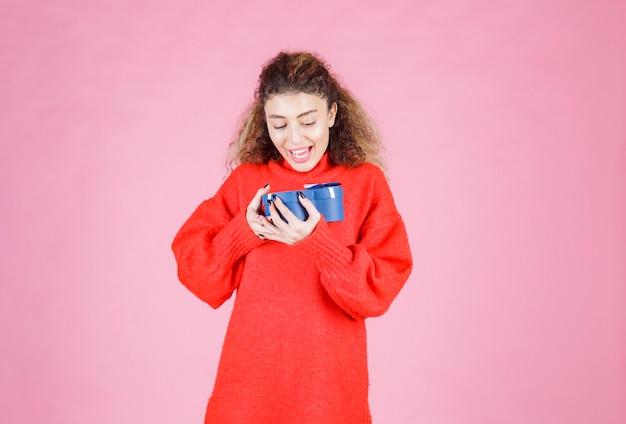 Kobieta trzyma pudełko w kształcie niebieskiego serca i wygląda na zdziwioną.