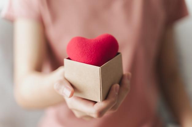 Kobieta trzyma pudełko z czerwonym sercem miłość ubezpieczenie zdrowotne darowizna szczęśliwy wolontariusz charytatywny