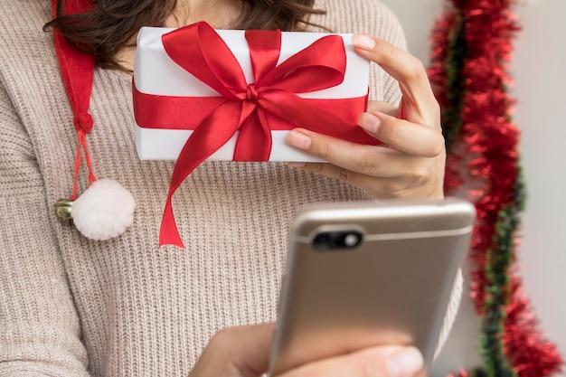 Kobieta trzyma pudełko z kokardą i pokazuje je smartfonowi. życzenia wesołych świąt online