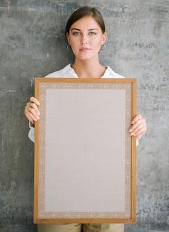 Kobieta trzyma pustą drewnianą ramkę na zdjęcia