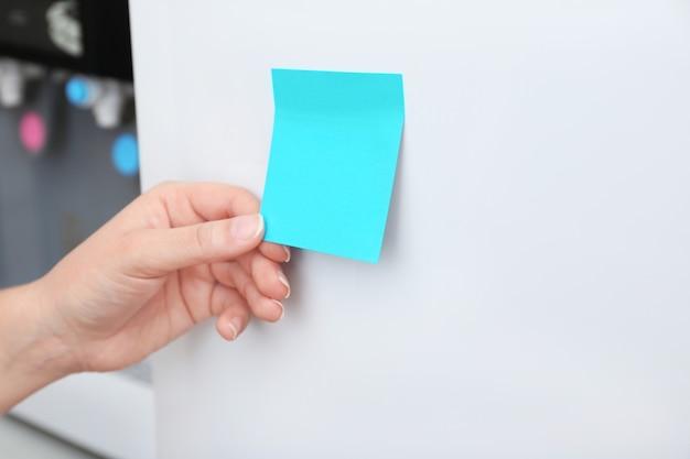Kobieta trzyma pustą notatkę na drzwiach lodówki, zbliżenie