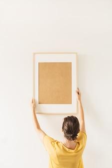 Kobieta trzyma pustą ramkę na zdjęcia