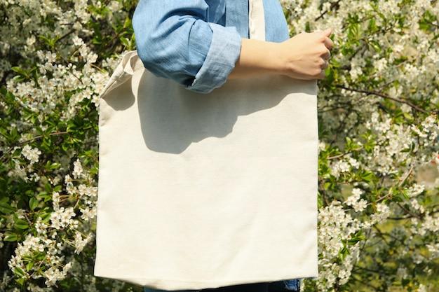 Kobieta trzyma puste płótno torby tkaniny. kwitnące wiosną