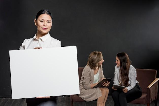Kobieta trzyma pusty arkusz papieru