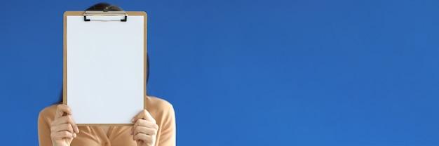 Kobieta trzyma pusty dokument w schowku w dłoniach przed twarzą