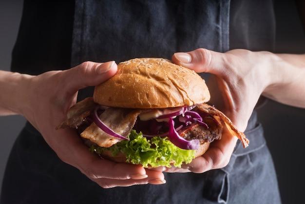 Kobieta trzyma pysznie wyglądającego hamburgera